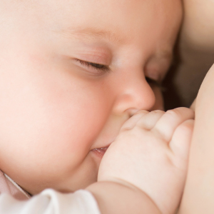 Mother breast feeding her baby with closed eyes